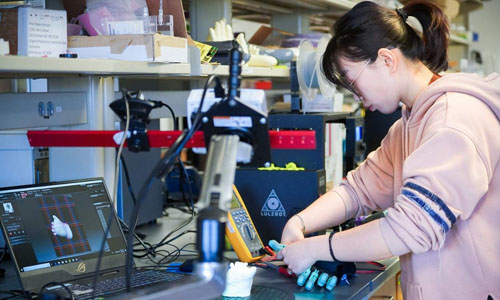 A grad student adjusting a 3D printed prosthetic